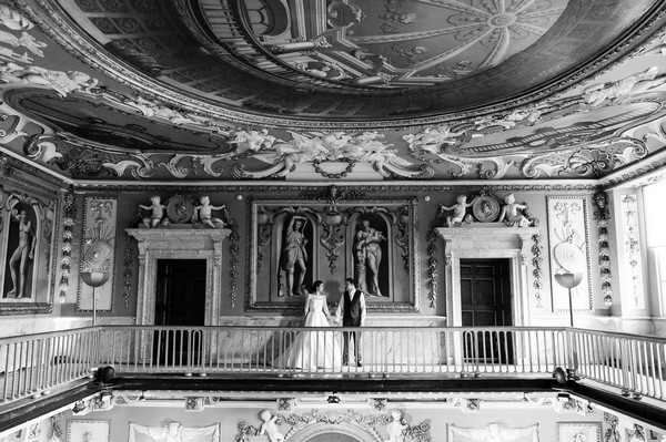 Bride and groom on balcony inside Moor Park Mansion