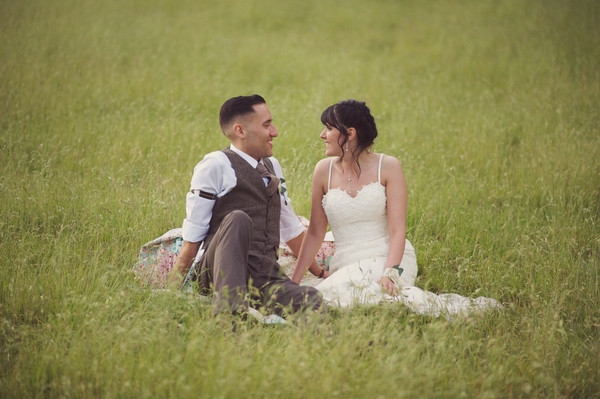 Bride and groom sitting on grass in field