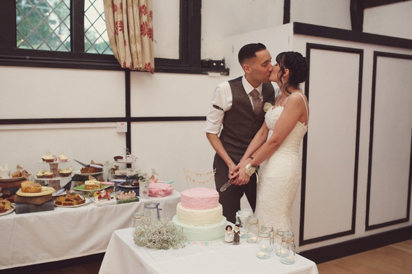 Bride and groom kiss as they cut the cake
