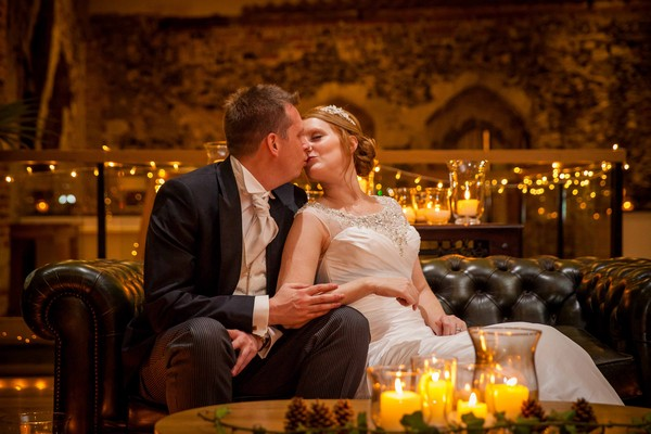 Bride and groom kissing on sofa - Picture by Amanda Karen Photography