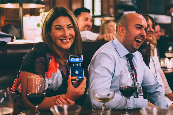 Wedding guest showing speech length time on phone