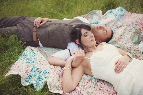 Bride and groom laying on rug on grass