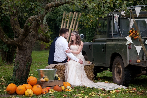 Bride and groom sitting by Land Rover in Derr Park at autumn