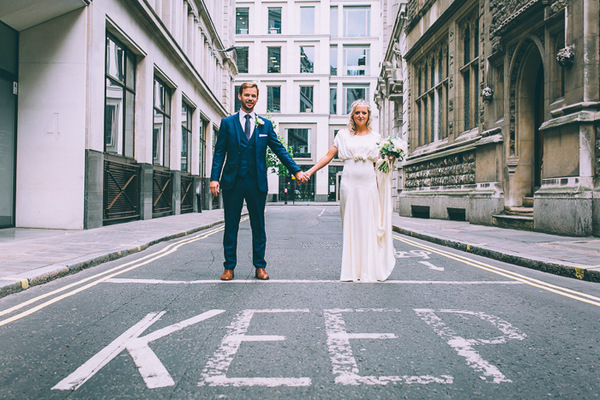 Bride and groom holding hands behind word KEEP written on road in London
