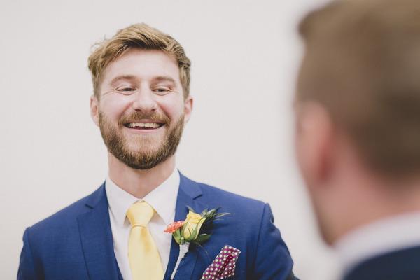 Groom in blue suit smiling