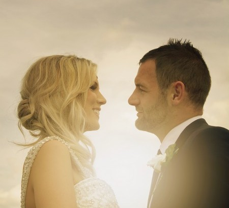 Bride and groom facing each other with sun shining between them - Picture by KTM Photography