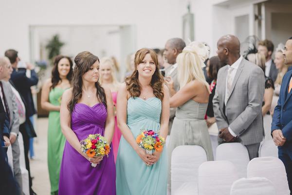 Bridesmaids walking down aisle in bright dresses