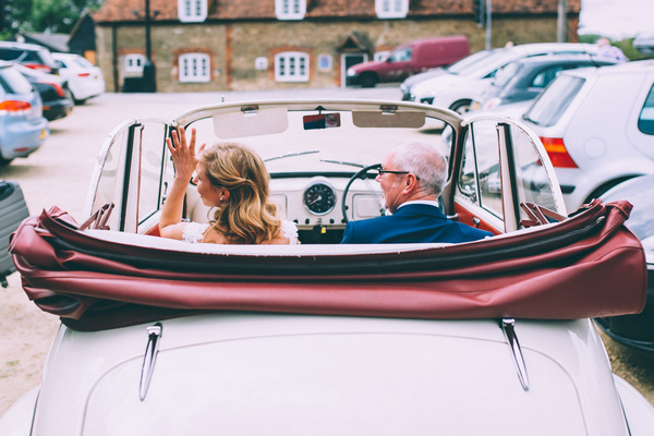 Father and bride in vintage Morris Minor wedding car