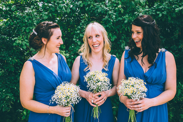 Bridesmaids in blue dresses with chamomile bouquets