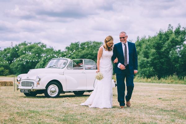 Father walking bride across field to wedding ceremony
