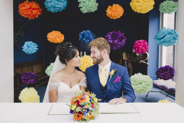 Bride and groom sign register in front of colourful backdrop