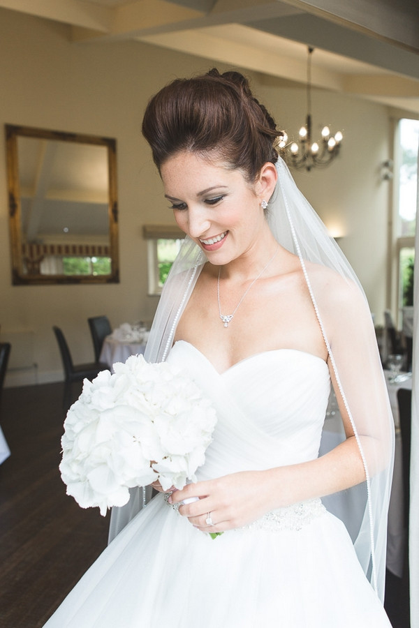 Bride smiling holding bouquet