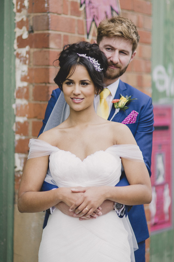 Groom behind bride with hands around her waist