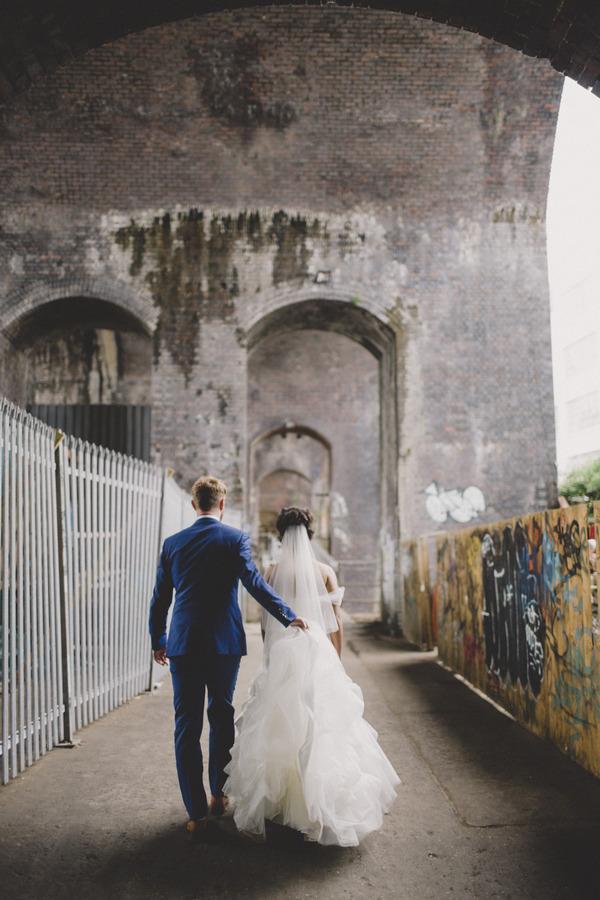 Bride and groom walking past graffiti wall in Birmingham