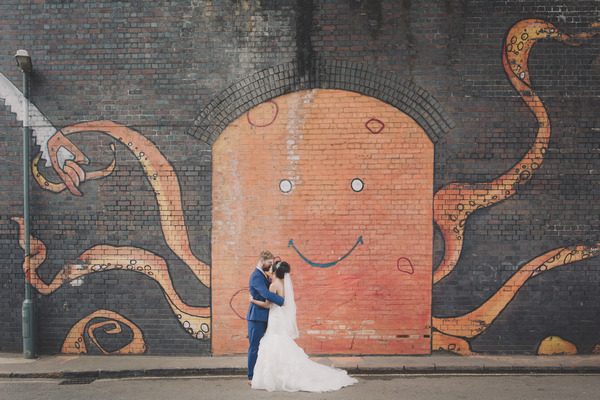 Bride and groom standing in front of wall with octopus graffiti