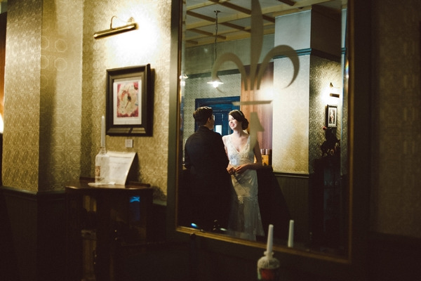 Reflection of bride and groom in bar mirror