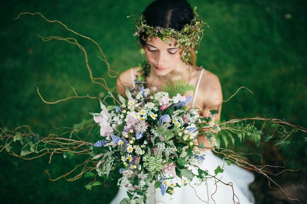 Bride with flower crown holding bouquet at Cosawes Barton