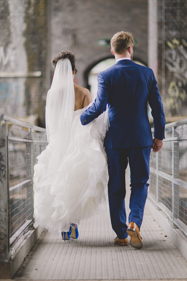Groom holding up bride's dress as she walks
