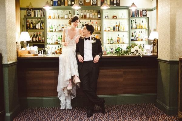 Retro bride sitting on bar with groom