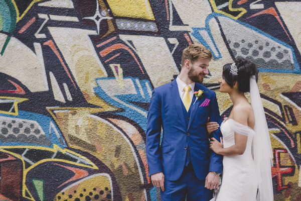 Bride and groom in front of graffiti covered wall