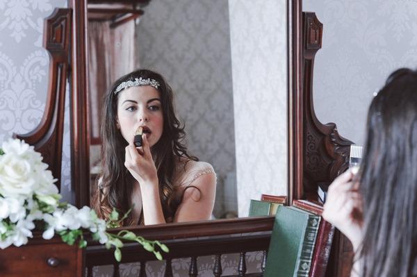 Retro bride doing lipstick in mirror