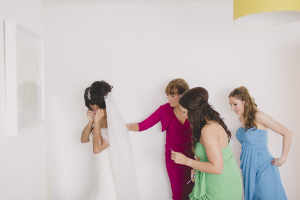 Bridesmaids helping bride with dress
