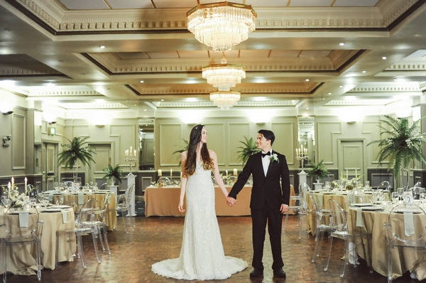 Bride and groom holding hands in ballroom