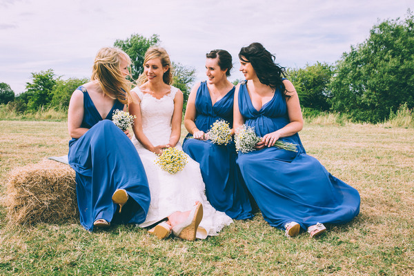 Bride sitting with bridesmaids in blue dresses