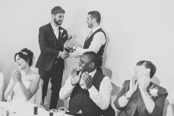 Best man handing groom gift