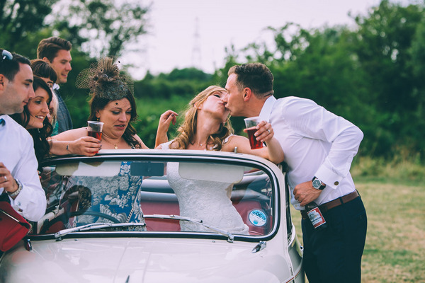 Bride and groom kiss in Morris Minor