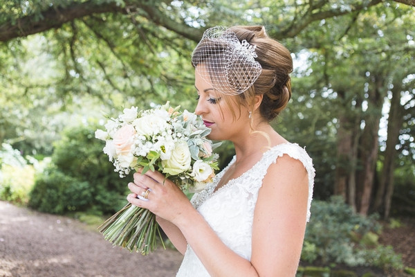 Bride with birdcage veil smelling bouquet