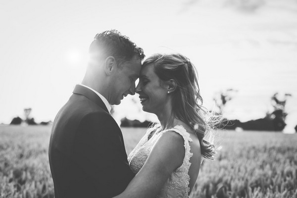 Bride and groom touching heads in field