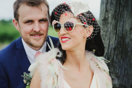 Groom with bride wearing birdcage veil and sunglasses