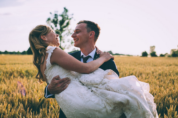 Groom carrying bride in corn field