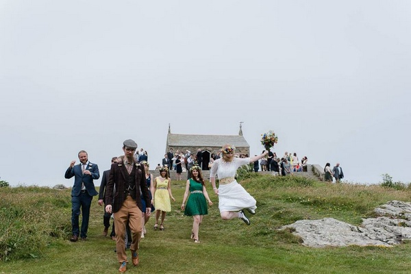 Bride jumping in air and clicking heels together as wedding guests walk down hill - Picture by Alexa Loy Photography
