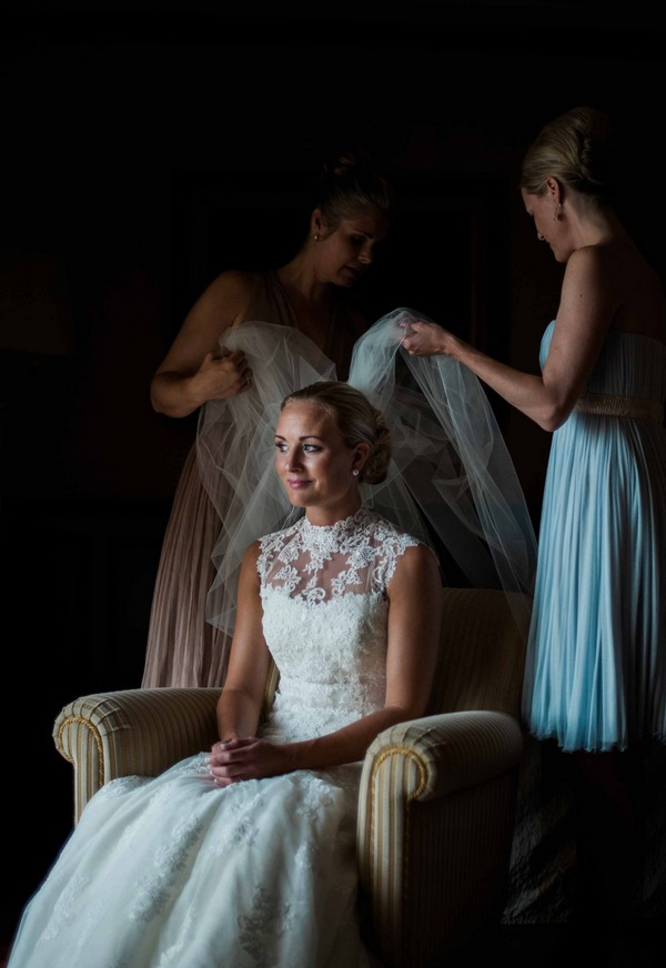 Bride sitting in chair putting veil on
