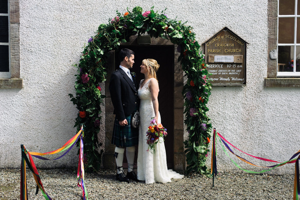 Bride and groom in front of entrance to Church of Scotland, Ardfern