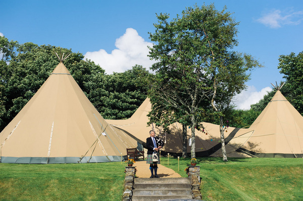 Bagpiper in front of tipis