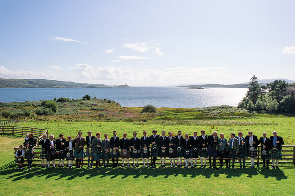 Bridal party in long line in front of Loch Melfort