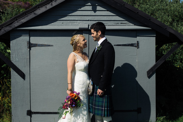 Bride and groom in front of shed
