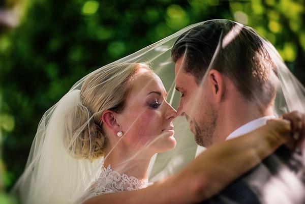 Bride and groom under bride's veil