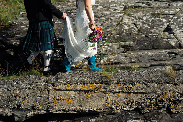 Bride in wellies walking across rocks
