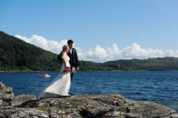 Bride and groom standing on rocks overlooking Loch Melfort