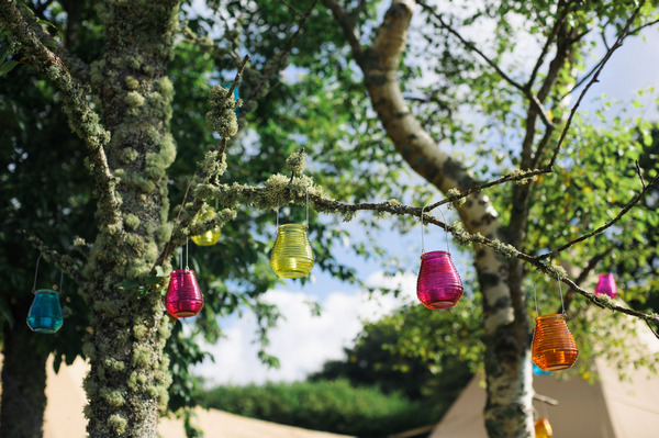 Coloured glass lanterns hanging in trees
