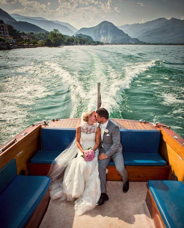 Bride and groom kissing on speedboat