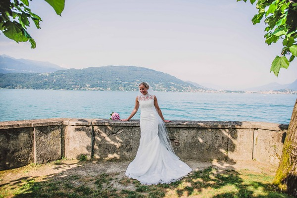 Bride leaning against wall by Lake Maggiore, Italy