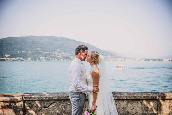 Bride and groom kissing by Lake Maggiore, Italy
