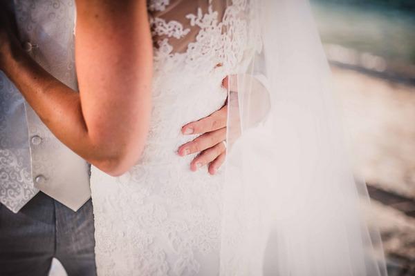 Groom's hand on bride's back