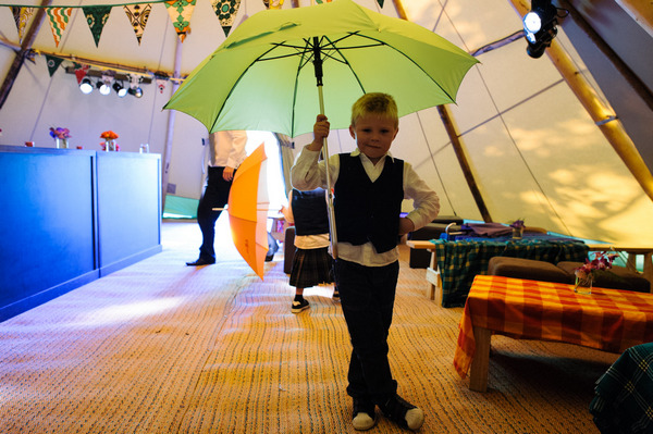 Young boy at wedding holding umbrella