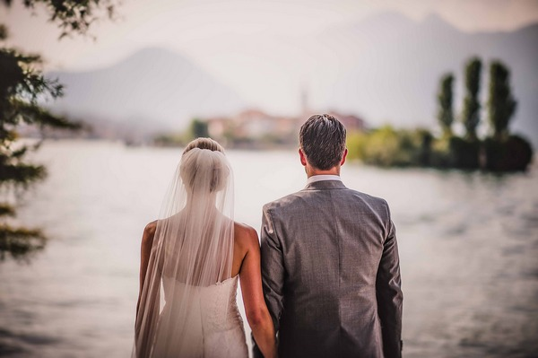 Bride and groom standing side by side by Lake Maggiore, Italy